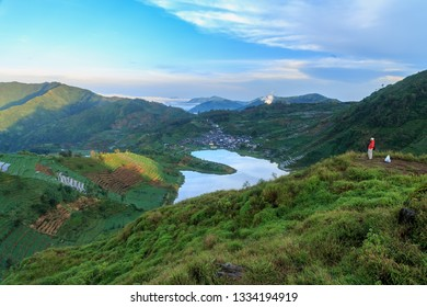 Dieng, central java / indonesia - april 26, 2014: a visitor enjoyed the morning scenery at the lake in Dieng surrounded by hills from the summit of Sikunir.