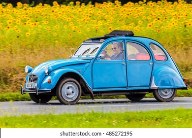 DIEREN, THE NETHERLANDS - AUGUST 12, 2016: Retro styled image of a Vintage Citroen 2CV on a local road in front of a field with blooming sunflowers in Dieren, The Netherlands