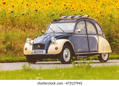 DIEREN, THE NETHERLANDS - AUGUST 14, 2016: Retro styled image of a Vintage Citroen 2CV on a local road in front of a field with blooming sunflowers in Dieren, The Netherlands