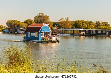 DIEREN, THE NETHERLANDS - AUGUST 23, 2016: Recreational houseboat used for vacations passing other houseboats on the river Vecht in Weesp, The Netherlands