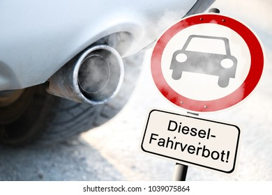 """Diesel driving ban Prohibition sign next to a car exhaust -  german road sign with the german text """"Diesel driving ban"""""""