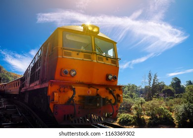 Diesel Electric Locomotives train moving on the Death Railway and Kra Sae Cave, is a railway bridge between the cliff and Khwae Noi river at Kanchanaburi, Thailand