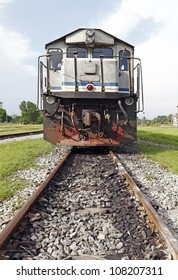 A diesel engine train head on a railway track in rural Malaysia.