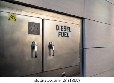 Diesel fuel sign on refueling station closed shut steel doors outside of building