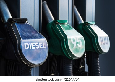Diesel text, 95 and 100 high octane and quality gasoline numbers on fuel pistols of gas station refueling stand - transportation, oil business or environmental pollution theme closeup background