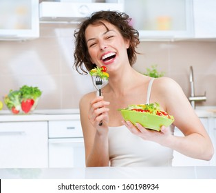 Diet. Beautiful Young Woman Eating Vegetable Salad in the Kitchen. Dieting concept. Healthy Vegan Food. Healthy Smiling Girl with Bowl of Salad and Fork. Weight Loss. Vegetarian Food