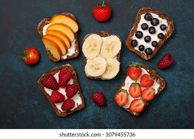 Diet breakfast. Toasts with cream cheese and fresh berries and fruits: banana, raspberry, blueberry, strawberry, peach. view from above