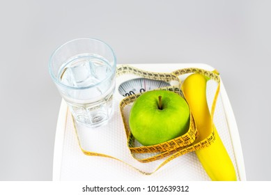 Diet concept. Apple banana glass of water tape measure