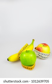 Diet concept. Apple and banana with tape measure
