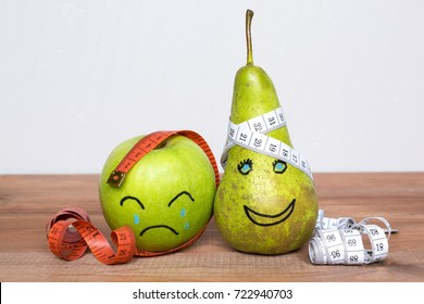 Diet concept, apple and pear with measuring types and drown sad and happy faces.