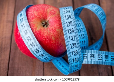 Diet concept Apple and tape measure closeup on wooden background