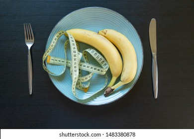 Diet concept - banana on plate with measuring tape