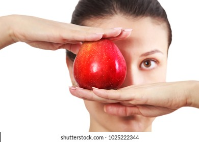 Diet concept. Brunette girl holding red apple at face level isolated on white background.