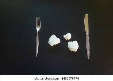 Diet concept - cauliflower on dark background with measuring tape