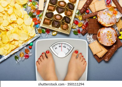 Diet concept. Feet of a young woman on bathroom scale and chocolate, jelly cubes, candies, chocolate bars, cookies, donuts, potato chips. Top view