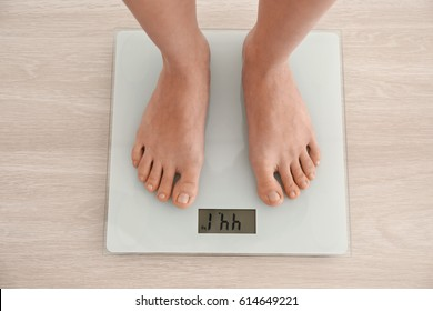 Diet concept. Female bare feet standing on scales