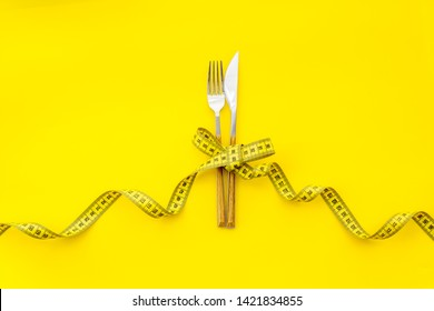 Diet concept with flatware and measuring tape for weight loss on yellow background top view