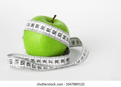 Diet concept with a green apple and measuring tape.