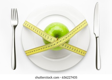 Diet concept, green apple on a white plate, yellow measuring tape, fork, knife, weight loss, healthy diet