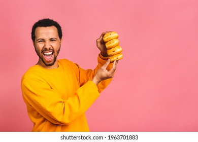 Diet concept. Hungry african american bearded man eating donuts isolated on pink background.