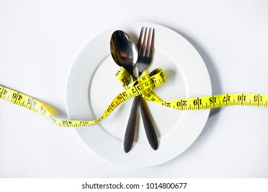 Diet concept - Measuring tape in empty plate on white table. Top view.