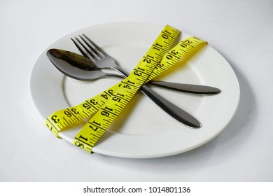 Diet concept - Measuring tape in empty plate on white table..