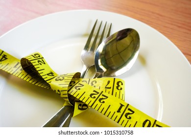 Diet concept - Measuring tape in empty plate on white table.