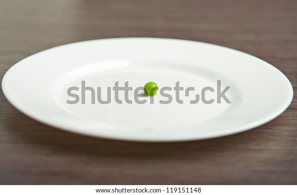 diet concept. one green pea on an empty white plate