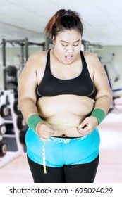 Diet Concept. Overweight young woman standing at gym center while measuring her belly with a measuring tape and looks unhappy