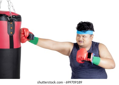 Diet concept. Portrait of a young overweight man doing workout by punching a boxing sack to lose weight, isolated on white background
