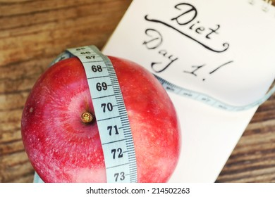 Diet concept with red apple, a notebook and blue measuring tape on wooden table