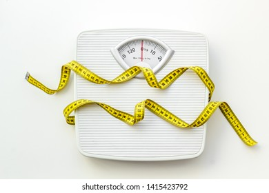 Diet concept with scale and measuring tape for weight loss on white background top view