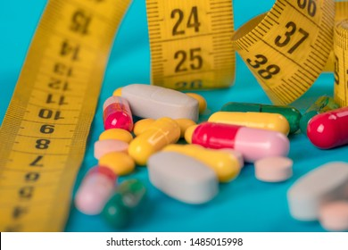 Diet concept; Slim by pills, dangerous for health. Centimeter tape and pills on a colored background with space for text. concept of losing weight, diet, fat burning, healthy eating. minimalism.