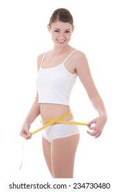 diet concept - smiling woman with beautiful body measuring her waistline with measurement tape isolated on white background