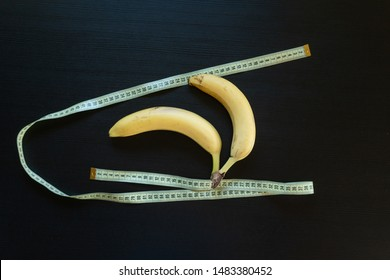 Diet concept - two bananas on the dark background with measuring tape. Banana and measuring tape