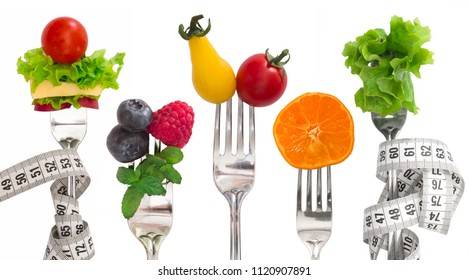 Diet concept, vegetables and fruit on forks isolated on white background