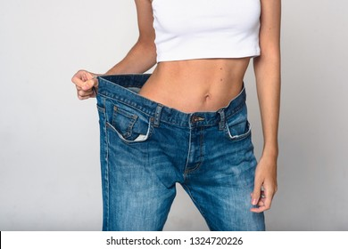 Diet concept and weight loss. Slim beautiful young blonde woman in oversize jeans on white background isolated
