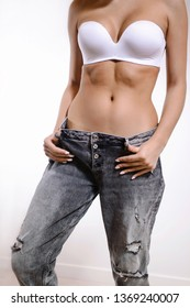 Diet concept and weight loss. Woman in oversize jeans posing on white background