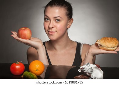 Diet concept: woman holding burger and apple.