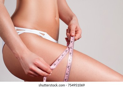Diet concept, woman measuring her leg with a measure tape