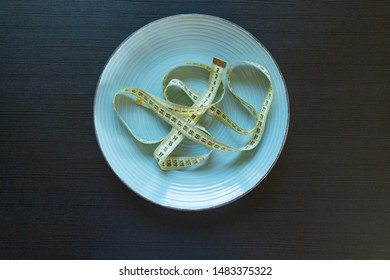 Diet concept - yellow measuring tape on plate