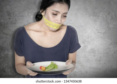 Diet concept. Young woman looks unhealthy while holding a plate of salad and covering her mouth with a measure tape
