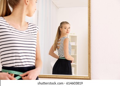 Diet concept. Young woman with measuring tape looking at mirror