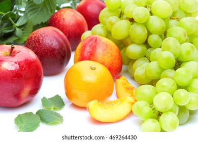 A diet detox food and healthy lifestyle concept: An aromatic colorful tasty delicious fruits. Sweet grapes orange peaches apples and aromatic mint. Top view. Isolated on white.