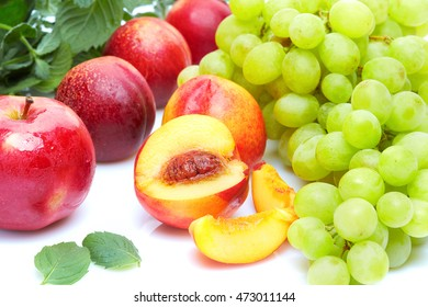 A diet detox food and healthy lifestyle concept: An aromatic colorful tasty delicious fruits. Sweet grapes peaches apples and aromatic mint. Top view. Isolated on white.