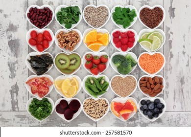 Diet detox super food & immune boosting food collection in heart shaped porcelain bowls over rustic wood background. Foods high in antioxidants, anthocaynins, omega 3, protein, vitamins & minerals.