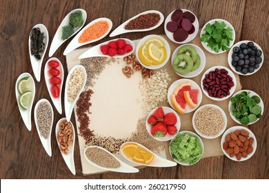 Diet detox super food selection in porcelain bowls on a speckled hemp paper notebook over oak wood background.