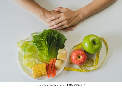 Diet, Dieting hand of woman choosing green salad, vegetable and red apple or fruits, choose eat food for good healthy, health when hungry, Weight loss vegetarian or vegan, isolated white background.