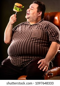 Diet failure of fat man eating fast food hamberger. Happy smile overweight person who In business chair eating huge hamburger on fork. Junk meal leads to obesity. Feast on occasion of feast.