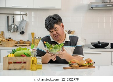 Diet failure of fat man eating fast food hamberger and he  Bored   to eat healthy salads.